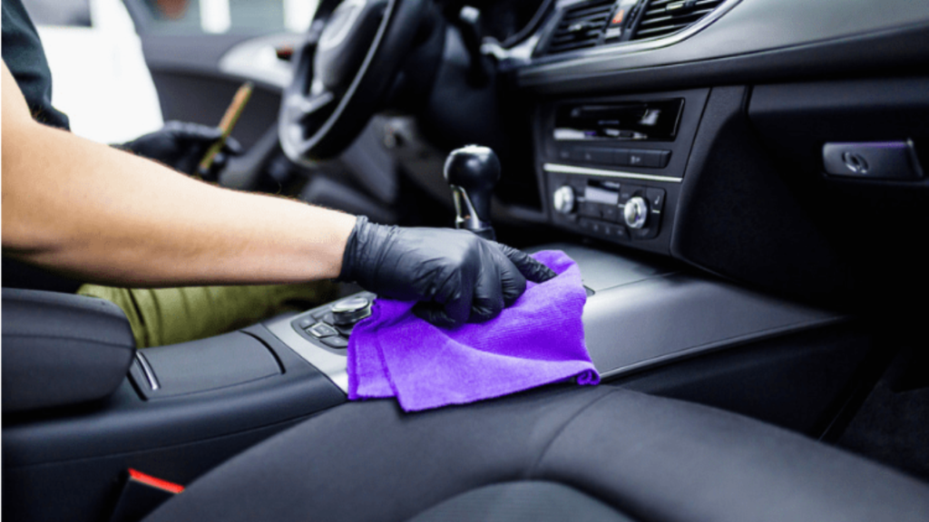 Employee wiping down a vehicle interior